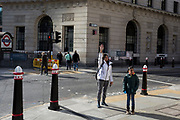 As the UK government lead by Prime Minister Boris Johnson urges Britons to avoid non-essential travel to EU countries, and to avoind contact with others in public places like pubs and theatres during the Coronavirus pandemic, Londoners keep calm and carry on with everyday activities on otherwise quiet streets in the financial district, on 16th March 2020, in London, England.