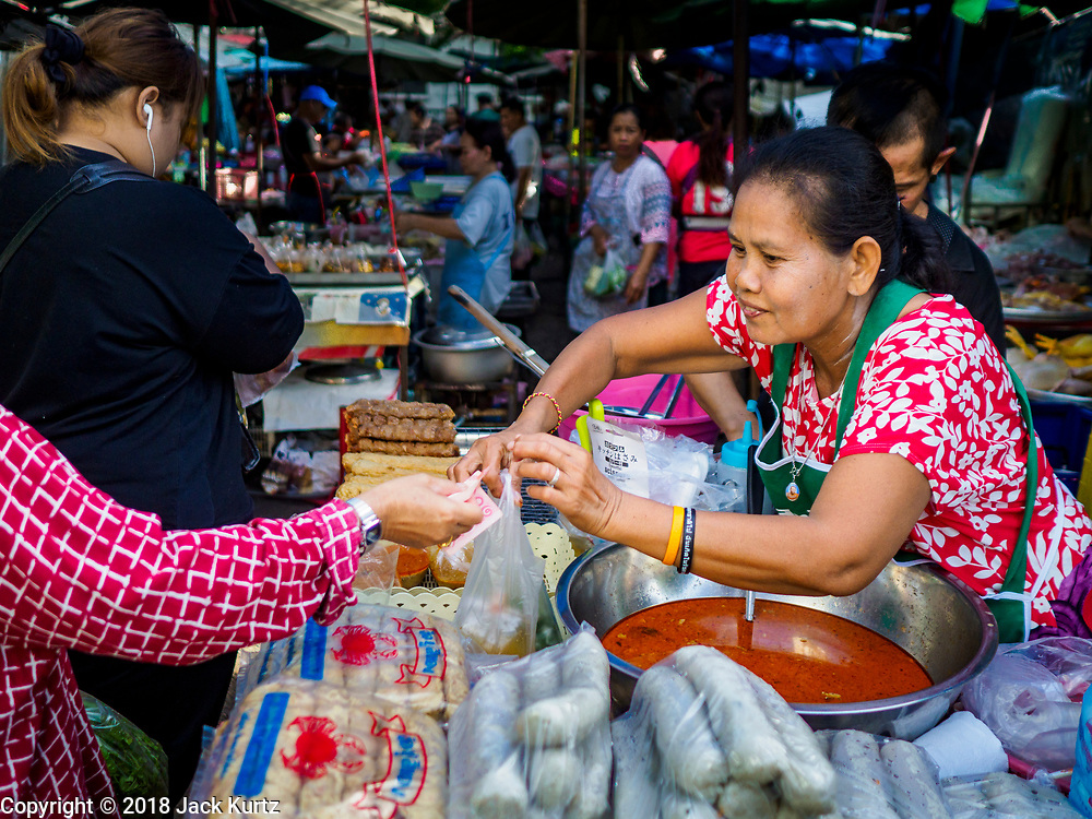 20 JUNE 2018 - BANGKOK, THAILAND: A food vender with her merchandise in plastic bags at Makkasan Market, a small local market in central Bangkok. Officials in Thailand are wrestling with Thais use of plastic bags. The issue became a public one in early June when a whale in Thai waters died after ingesting 18 pounds of plastic. In a recent report, Ocean Conservancy claimed that Thailand, China, Indonesia, the Philippines, and Vietnam were responsible for as much as 60 percent of the plastic waste in the world's oceans.    PHOTO BY JACK KURTZ