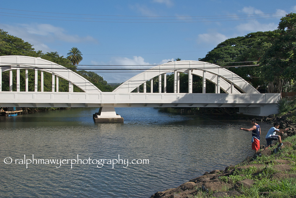 Locals fishing along the bank at Anahulu Bridge, Haleiwa, North Shore, Oahu, Hawaii. The Anahulu bridge is a landmark on the picturesque North Shore.