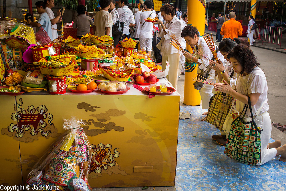 17 OCTOBER 2012 - BANGKOK, THAILAND:   People pray and make offerings during the Vegetarian Festival at an altar in Wat Mangkon Kamalawat, one of the largest Chinese shrines in Thailand. The Vegetarian Festival is celebrated throughout Thailand. It is the Thai version of the The Nine Emperor Gods Festival, a nine-day Taoist celebration celebrated in the 9th lunar month of the Chinese calendar. For nine days, those who are participating in the festival dress all in white and abstain from eating meat, poultry, seafood, and dairy products. Vendors and proprietors of restaurants indicate that vegetarian food is for sale at their establishments by putting a yellow flag out with Thai characters for meatless written on it in red.      PHOTO BY JACK KURTZ
