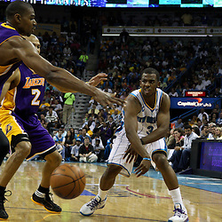 April 24, 2011; New Orleans, LA, USA; New Orleans Hornets point guard Chris Paul (3) passes as Los Angeles Lakers point guard Derek Fisher (2) and center Andrew Bynum (17) defend during the fourth quarter in game four of the first round of the 2011 NBA playoffs at the New Orleans Arena. The Hornets defeated the Lakers 93-88.   Mandatory Credit: Derick E. Hingle