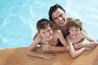 Portrait of father with two sons (5-11) in swimming pool elevated view