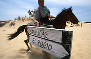 """A horseman rides past a sign to El Rocio and Sanlucar. The pilgrim route of the Hermandade de Sanlucar de Barrameda from Sanlucar across the Parque Donana to El Rocio, Huelva Province, Andalusia, Spain...El Rocio follows on from Semana Santa - Easter week and the various spring ferias, of which Seville's Feria de Abril (April) is the biggest. The processions to the (Hermitage) Hermita de El Rocío, at Pentecost, is the most famous (Romeria) pilgrimage in the Andalusian region, attracting nearly a million people from across Andalusia, Spain and the world. The cult started off in the 13th century when a statue of the virgin Mary was apparently found in a tree trunk in the Donana Park. What was first a local devotion at Pentecost by local pilgrim brotherhoods """"hermandades"""" became by the 19th century into dozens of fraternities developed from such as Cadiz, Selville and Huelva. Some walk for several days, others travel with oxen drawn wagons or on horseback, with traction engines and all terrain vehicles, camping along the trail they take. They wear Andalusian costumes, tight breeches, boots, short jackets and frilly flamenco skirts. Many festivities, flamenco dance, laments, songs and music are combined with religious prayers. Devout pilgrims walk as a penance, keeping vows of silence. An emblem of the immaculate conception (sin peche) is carried. On the Pentecost after the stroke of midnight on the whit Sunday the virgin Mary is carried from the church through the streets of El Rocio by each hermandade to visit each brotherhood's shrine."""