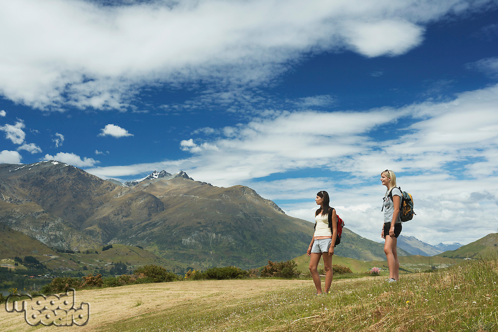 Two women hiking in hills near mountains