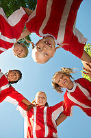 Five children soccer players (7-9 years) huddling, view from below, portrait