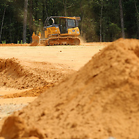 A bulldozer works at moving dirt and preparing the lot for the future Eight Days of Hope Headquarters.