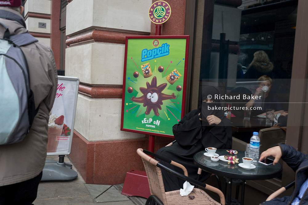 A Muslim lady sits next to an ad for sweets (candy), on 4th May 2017, in London, England.
