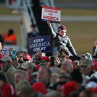 "A young fan of President Trump holds up a ""Stand Up for America"" sign as during the president's speach Monday afternoon at the Tupelo Regional Airport."
