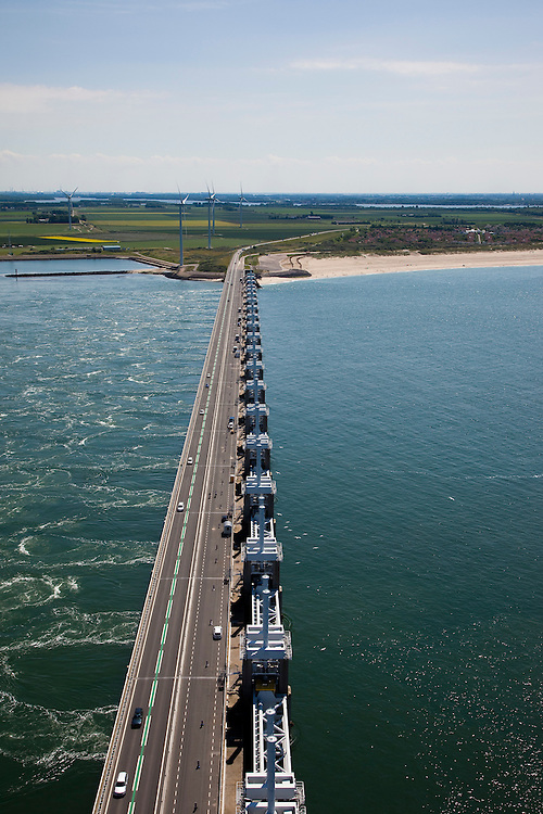 Nederland, Zeeland, Oosterschelde, 12-06-2009; Stormvloedkering met verkeersweg ter hoogte van het sluitgat Roompot, gezien naar Noord-Beveland.Links de Oosterschelde, rechts de Noordzee, het water stroom met vloed onder de geopende kering door. .Close-up storm surge barrier in Oosterschelde (East Scheldt), hydraulic cylinders for the slides and sight on the pillars. Under normal circumstances the barrier is open to allow for the tide to enter and exit. In case of high tides in combination with storm, the slides are closed. North Sea with high tide on the right..Swart collectie, luchtfoto (25 procent toeslag); Swart Collection, aerial photo (additional fee required).foto Siebe Swart / photo Siebe Swart
