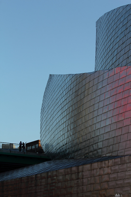 A couple stand on the Puente de la Salve and admire the Frank Gehry designed Guggenheim in Bilbao.