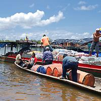 Hombres cargando barriles de gasolina en el Puerto de Samariapo, estado Amazonas, Venezuela. ©Jimmy Villalta