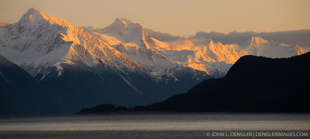 The final rays of the setting sun at sunset bath the tops of the mountains along the Chilkoot Inlet of the Lynn Canal taken just outside Haines, Alaska.