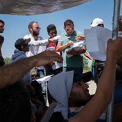 Refugees distribute registration documents at the reception center near the Greece-Macedonia border on August 25, 2015.  After crossing into Macedonia the refugees travel north to border with Serbia where they will continue their journey to other European states.