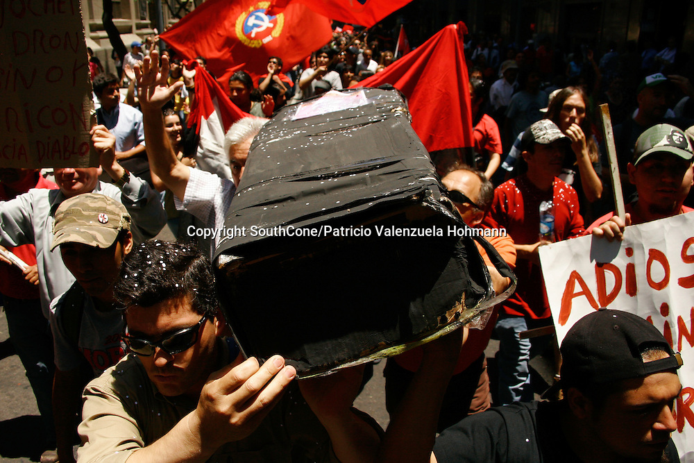 People carries a fake Pinochet's coffin, as they threw it to the Mapocho river.<br /> December 2006, The Chilean Dictator Augusto Pinochet died in Santiago Chile. As news spread thousands went out the streets either to celebrate o mourn Pinochet who lead the 1973 coup that overthrew the democratically elected president Salvador Allende. Pinochet's 17 year regime killed and disappeared around 4.000 people, tortured and exile around 20.000. On 1989 he lost elections and democracy was regained. He died on late December 2006. December 2006, The Chilean Dictator Augusto Pinochet died in Santiago Chile. As news spread thousands went out the streets either to celebrate o mourn Pinochet who lead the 1973 coup that overthrew the democratically elected president Salvador Allende. Pinochet's 17 year December 2006, The Chilean Dictator Augusto Pinochet died in Santiago Chile. As news spread thousands went out the streets either to celebrate o mourn Pinochet who lead the 1973 coup that overthrew the democratically elected president Salvador Allende. Pinochet's 17 year.