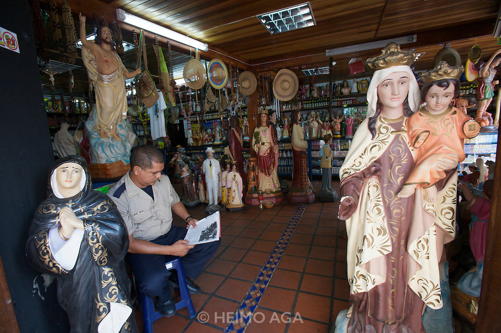 Security guard at a shop with Catholic statues.