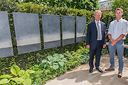 Matthew Keightley (r) and Owen Paterson, Minister for Agriculture, on the Hope on the Horizon garden.  The<br /> &lsquo;Hope on the Horizon&rsquo; garden in aid of Help for Heroes: produced by building and landscaping firm Farr and Roberts&rsquo;, making their debut; designed by Matthew Keightley (29), as a result of his brother Michael&rsquo;s involvement with the armed forces, having served on four tours to Afghanistan and due for his fifth this year; and sponsored by the David Brownlow charitable foundation. The garden layout is based on the shape of the Military Cross, the medal awarded for extreme bravery. Granite blocks will represent the soldiers&rsquo; physical wellbeing and the planting represents their psychological wellbeing at various stages of their rehabilitation. Both evolve through the garden from a rough, unfinished, over-grown beginning through to a perfectly sawn, structured end. An avenue of hornbeams draws the attention through the entire garden to a sculpture resembling a hopeful horizon; a reminder to the soldiers that they all have a bright future ahead. As well as areas to recline and reflect, the garden offers focal points all the way through. Cool, calming colours are used throughout, helping to emphasise the fact that it will be a serene, contemplative space. After the Show, the garden will be moved and set within the grounds at Help for Heroes Recovery Centre at Chavasse VC House in Colchester, Essex. The garden will offer a serene, peaceful haven to contemplate and inspire a bright future and to support the challenging journey to recovery. The Chelsea Flower Show 2014. The Royal Hospital, Chelsea, London, UK.  19 May 2014.  Guy Bell, 07771 786236, guy@gbphotos.com