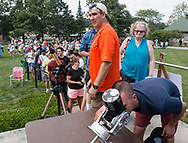 Middletown, New York - People line up on Alumni Green at SUNY Orange to watch a partial solar eclipse through a solar telescope amd another telescope, at right, with a solar filter, on Aug. 21, 2017.