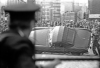 The Silver Jubilee visit of Queen Elizabeth II to N Ireland on 10th & 11th August 1977 sparked serious rioting in Belfast as those opposed to the visit tried to reach the city centre. Policeman watches as rioters overturn a sports car.  197708100074g<br />
