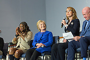 Democratic presidential candidate Hillary Rodham Clinton smiles as former Congresswoman Gabrielle Giffords, right, speaks during the Breaking Down Barriers Forum on gun violence at Central Baptist Church February 23, 2016 in Columbia, South Carolina. The event was attended by mothers who lost their children to gun violence and police incidents.