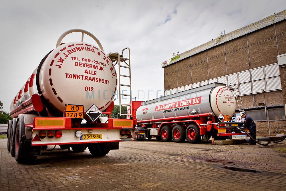Een medewerker van de firma Rumping in Beverwijk tijdens het lossen van zoutzuur.