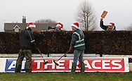Plumpton, UK. 12th December 2016. <br /> Groundsmen in festive Santa Claus hats prepare a fence for the next race<br /> &copy; Telephoto Images / Alamy Live News