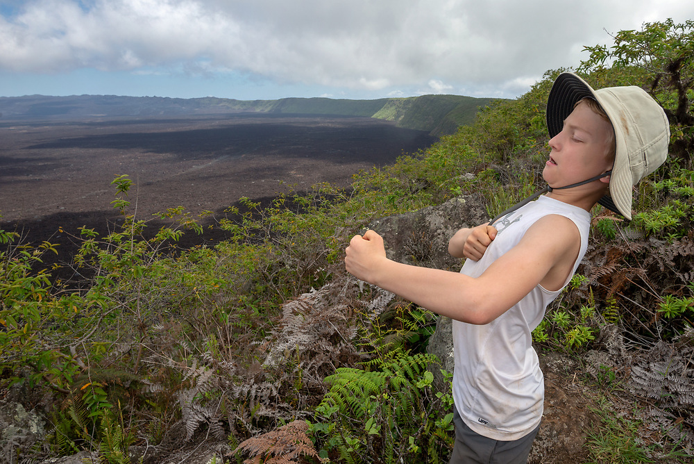 Boy playfully beating his chest on the rim of Sierra Negra Volcano, Galapagos Islands, Ecuador.