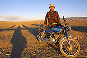 GOBI DESERT, MONGOLIA..08/24/2001.Gobi Gurvansaikhan National Park..Motocycle driver in front of Khongoryn Els sand dunes at sunset..(Photo by Heimo Aga)