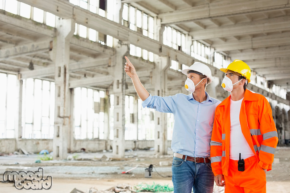 Male construction worker discussing at site