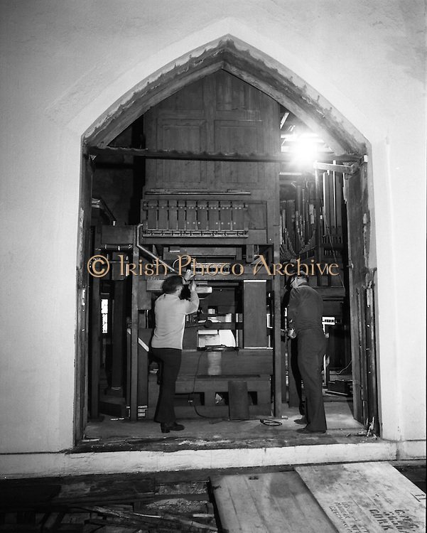 Pipe Organ Dismantling at Aungier Street.  (K86).1977..01.02.1977..02.01.1977..1st February 1977..A pipe organ built around 100 years ago for St Peter's Church (Church of Ireland),at Whitefriar / Aungier Street was being dismantled by Mr Gerry Smith and Mr Sam Wright of Dublin Organ Works. The organ was being dismantled for transfer to St Michael's Church,(Roman Catholic),in Blackrock,Co Cork..Image shows the innards of the organ after the organ pipes and fascia have been removed from the organ.
