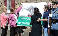 NEWTOWN, PA - APRIL 22:  Family members help to unveil the new sign during a dedication ceremony to rename part of the Newtown Bypass in honor of former Newtown Borough Police Officer Brian Gregg at Newtown Borough Hall April 22, 2014 in Newtown, Pennsylvania. Gregg was killed in the line of duty during the shootings at St. Mary Medical Center in 2005. (Photo by William Thomas Cain/Cain Images)