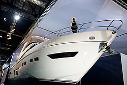 © Licensed to London News Pictures. 06/01/2017. London, UK. A model poses on a Princess yatch whilst sailing enthusiasts visit the London Boat Show at ExCel London whilst on Friday, 6 January 2017. Until the 15th of January the London Boat Show will showcase, demonstrate and sell maritime equipment ranging from luxury yachts to dinghies. Photo credit: Tolga Akmen/LNP