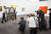 UNITED KINGDOM, London: 09 April 2018 Photographers take pictures as 'Femme au Chien' by Pablo Picasso valued at $12-18 Million is moved into position at the Impressionist and Modern and Contemporary Art preview. The Impressionist and Modern art sale will be held in New York on 14th May. Sotheby's Impressionist and Modern Art Sale, London, UK- 9 Apr 2018 Rick Findler  / Story Picture Agency