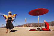 Peter Menzel photographs Tokyo-based photographer Vincent Huang who used the giant Burning Man structure and revelers as a backdrop for his photographs of a traditional Japanese tea ceremony with performance artist Ken Hamazaki for a Japanese magazine. Burning Man is a performance art festival known for art, drugs and sex. It takes place annually in the Black Rock Desert near Gerlach, Nevada, USA.