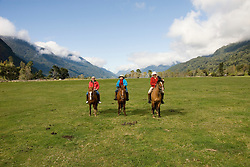 Chile, Lake Country: People riding horses at Peulla in a meadow in the Andes..Photo #: ch608-33254..Photo copyright Lee Foster www.fostertravel.com, lee@fostertravel.com, 510-549-2202.