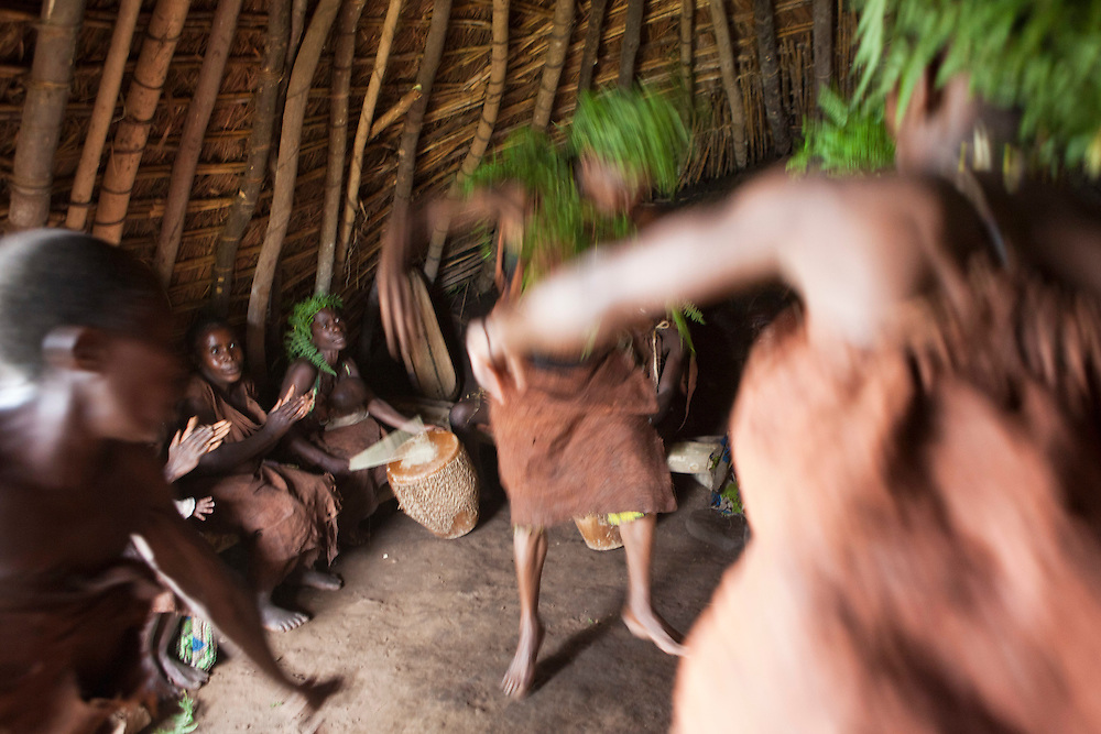 Batwa members act out a story with music song and dance in the village house of Mukuno. They are a group of Batwa pygmies from the Bwindi Impenetrable Forest in Uganda. They were indigenous forest nomads before they were evicted from the Bwindi Impenetrable Forest when it was made a World Heritage site to protect the mountain gorillas. The Batwa Development Program now supports them.