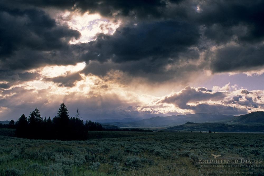 Sunbeams at sunrise through dark storm clouds over the prairie, Grand Teton National Park, Wyoming