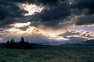 Sunbeams at sunrise through dark storm clouds over the prairie, Grand Teton National Park, Wyoming