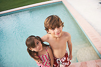Boy (7-9) and girl (5-6) embracing at edge of swimming pool elevated view