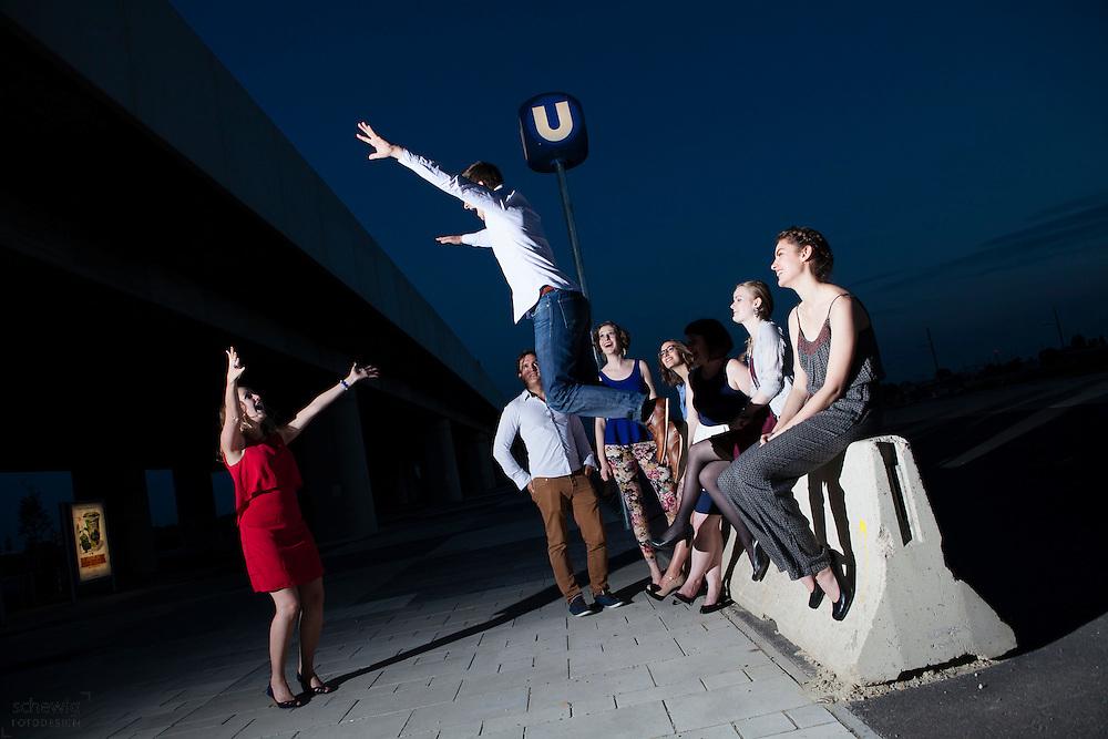 Österreich, Wien, Gruppe junger Leute vor U-Bahnstation, gemeinsam etwas unternehmen, Freizeit genießen, Spaß haben, auf dem Weg zur Party, Sommer, Nacht