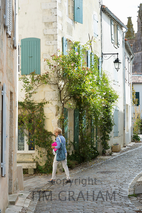 Typical street scene quaint house with shutters traditional architecture, woman walking, St Martin de Re, Ile de Re, France