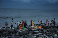 Local families gather on Pondicherry's waterfront, where the pray to Lord Ganesha for the Ganesh Chaturthi Festival, and then young men, seen in the water throw their earthen Ganesha statues into the sea.  Pondicherry, India.    According to Hindu tradition, like these idols (murtis) the gentle, nurturing goddess, Parvati, created the original Ganesh out of clay, before he was beheaded by her husband's, the god Shiva's, sword and replaced by the head of an elephant.