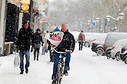 Met een bos bloemen in de hand fietst een man door de sneeuw over de Oudegracht in Utrecht.<br /> <br /> A man is cycling at the Oudegracht Utrecht in the snow with flowers in his hands.
