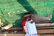 A girl laughs while doing her homework in the West Point slum of Monrovia, Montserrado county, Liberia on Monday April 2, 2012.