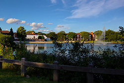 A building with a tent for a party sits across a lake with a fountain.  The lake has a split rail fence part way around it for safety. There are plenty of trees and foliage on the property and a bright blue sky with white clouds as an accent to this wonderful inviting screen.<br /> <br /> This image was produced in part utilizing High Dynamic Range (HDR) processes. It should not be used editorially without being listed as an illustration or with a disclaimer. It may or may not be an accurate representation of the scene as originally photographed and the finished image is the creation of the photographer.