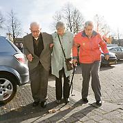 Foto: David Rozing  Etten Leur Ouderen, 1 iets jongere dame begeleid 2 ouderen, broze gezondheid, broos, broze, wankele tred, wankel, instabiel, bewegen, lopen, helpen, ondersteunen, ondersteuning, wandelstok. Foto: David Rozing