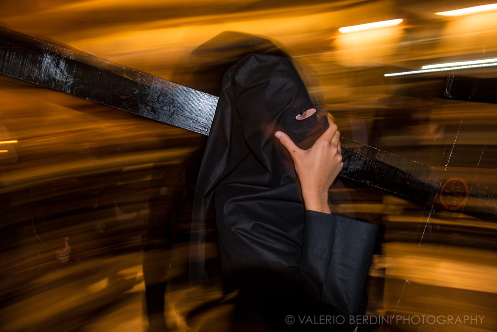 """San Isidoro Brotherhood in the evening of Good Friday in Cuna, a central street in Sevilla. Here """"Nazarenos"""", dressed with the """"capirote"""" and a full black tunic  make penance carrying along the procession either long (and heavy) Paschal candles or wooden crosses."""