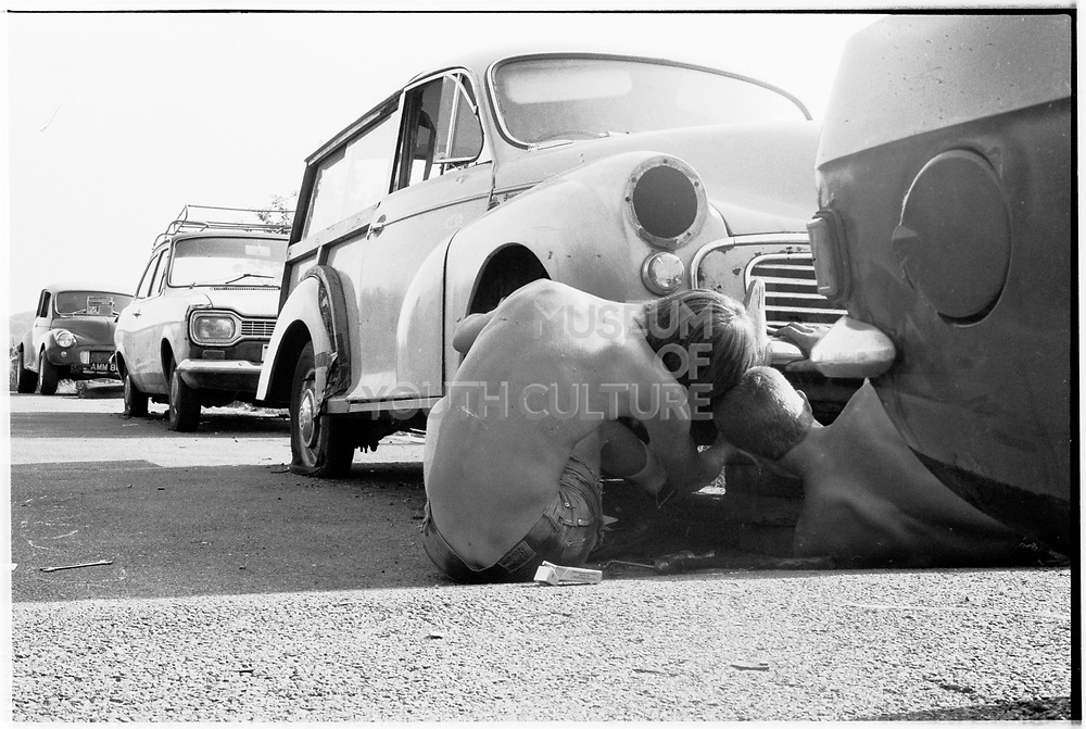 Two boys looking under car, London. 1980s.
