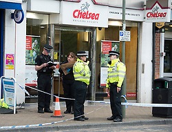"***LNP BEST OF WEEK SELECTION*** © London News Pictures. 07/05/2013. Sunbury-On-Thames, UK. Police officers carrying evidence bags outside Chelsea Building Society in Sunbury-on-Thames, in Surrey, which was robbed earlier today (Wed). 55-year-old escaped prisoner Michael Wheatley AKA ""Skull Cracker"", who was arrested in east London, is alleged to have carried out the robbery. Photo credit: Ben Cawthra/LNP"