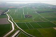 Nederland, Noord-Holland, Gemeente Wieringen, 28-04-2010; het voormalige eiland Wieringen gezien naar de polder Wieringermeer (li). Amstelmeer, Amstelmeerdijk en Balgzand aan de horizon. .Het Amstelmeerkanaal (ringvaart van de polder) volgt de rand van het vroegere eiland. Er zijn plannen om Wieringen weer een (quasi)eiland te maken door het verbreden van het Amstelmeerkanaal tot een meer (Wieringerrandmeer). De plannen zijn omstreden omdat ze ten koste zullen gaan van landbouwgrond en boerenbedrijven..The former island Wieringen seen in the direction of the polder Wieringermeer (left)..The Amstelmeer channel (ring canal of the polder) follows the edge of the former island. There are plans to restore the island character of Wieringen by broadening the channel (creatng a lake). The plans are controversial because they imply loss of agricultural land and farms..luchtfoto (toeslag), aerial photo (additional fee required).foto/photo Siebe Swart
