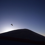 A competitor in action at sunrise during the Women's Slopestyle competition at the Burton New Zealand Open 2011 held at Cardrona Alpine Resort, Wanaka, New Zealand, 10th August 2011. Photo Tim Clayton